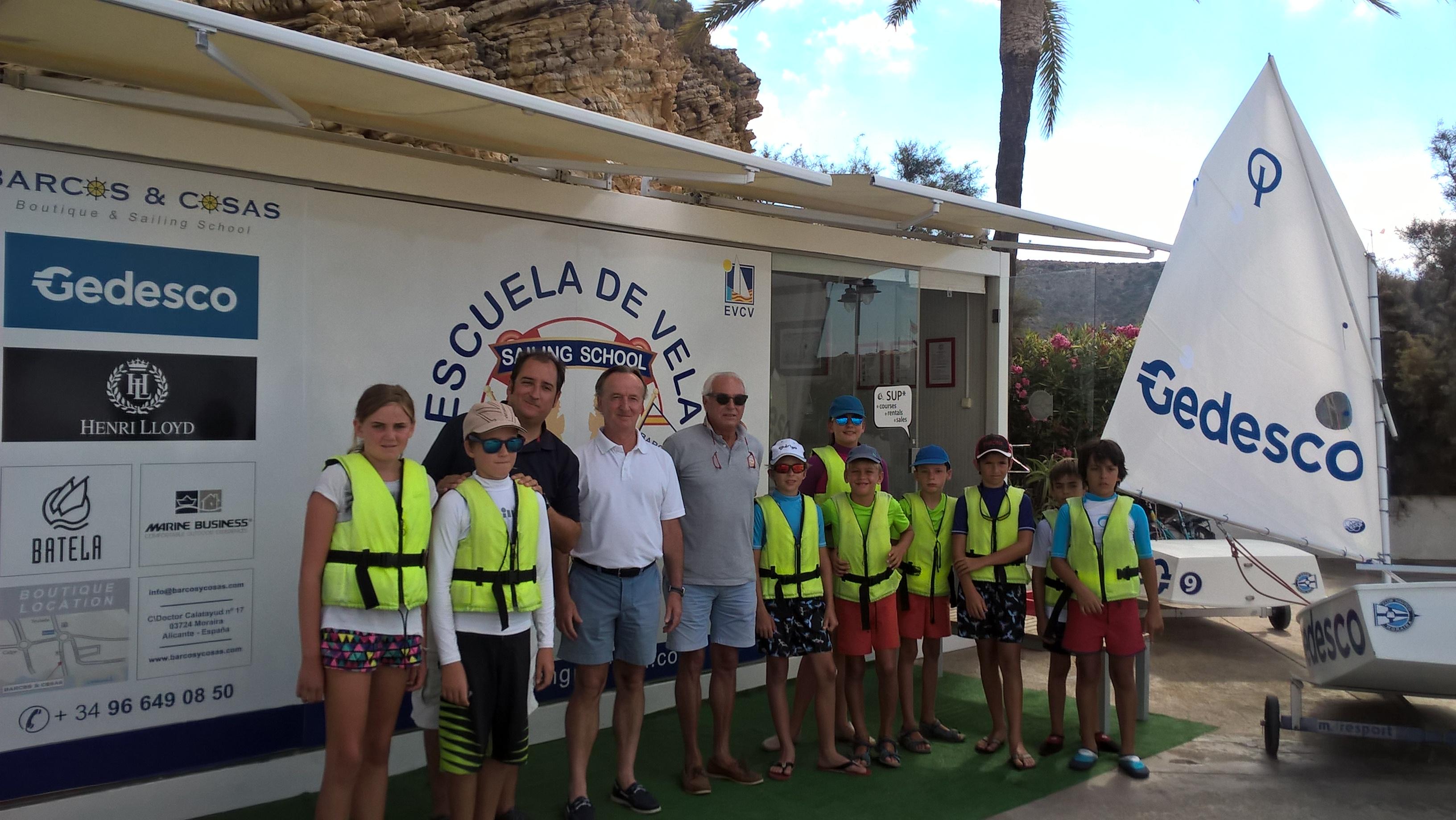 Andrés Rivero ( Barcos & Cosas ), Antonio Aynat ( Gedesco ) y Ramón Martí ( C.N. Moraira ) posan junto con alumnos de la escuela en su visita al centro de Vela & SUP del club por parte del Consejero delegado de GEDESCO.